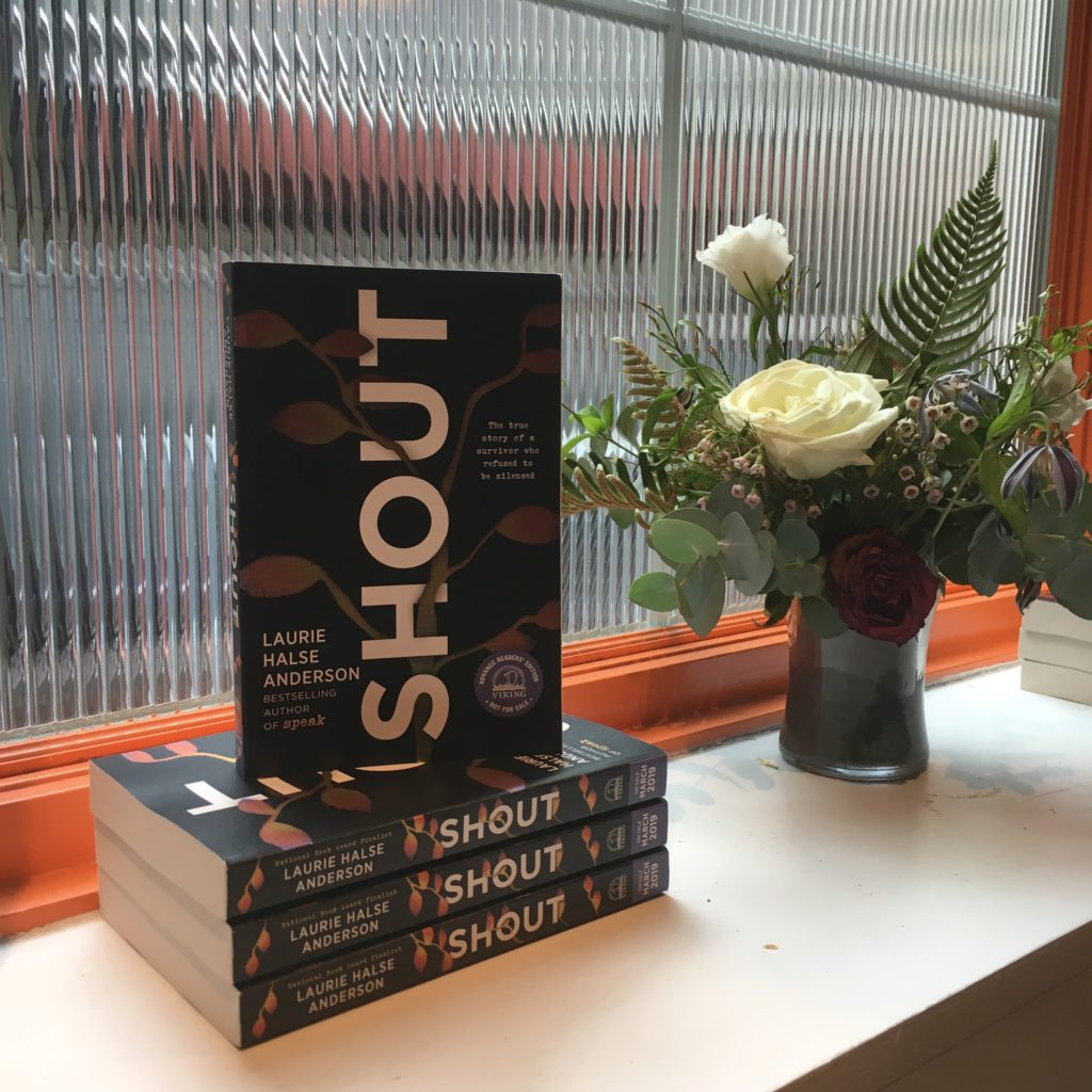 a stack of galleys of SHOUT displayed next to a vase of white roses and ferns